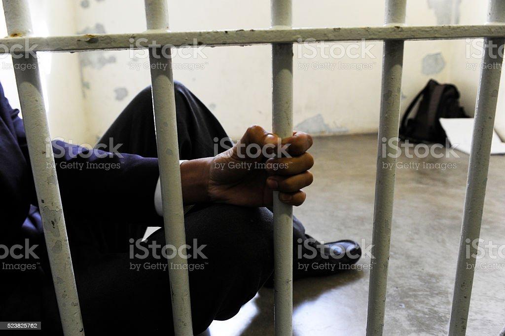 Prisoner grabs bars of prison cell stock photo