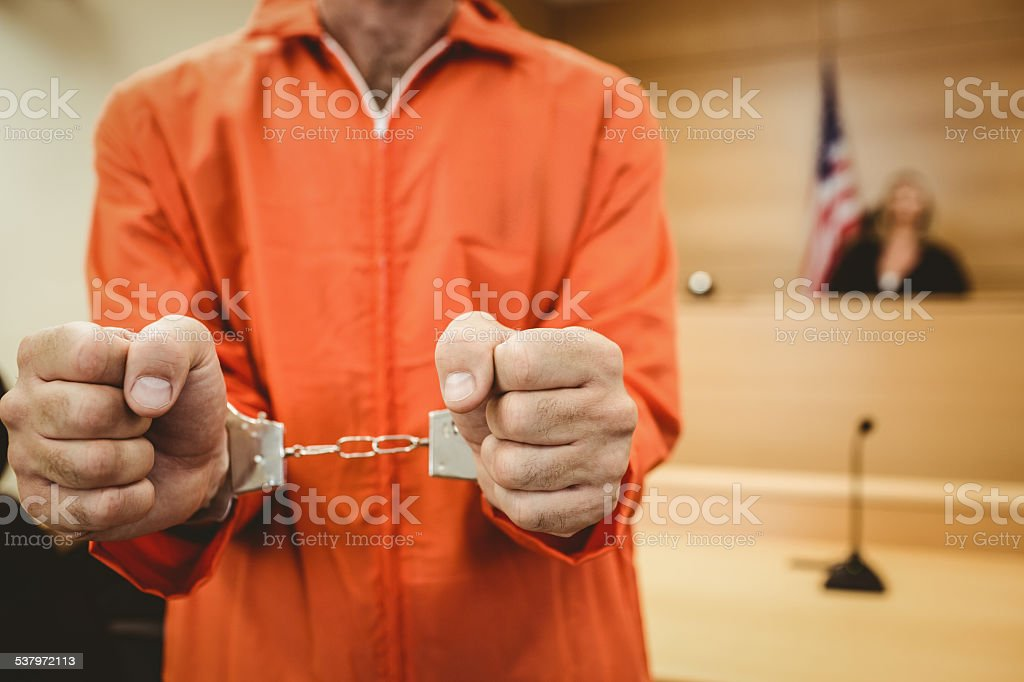 Prisoner in handcuffs clenching fists stock photo