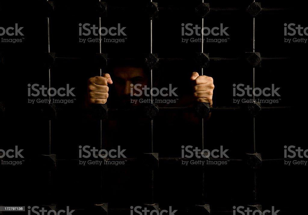 Prisoner pulling on bars with both hands in dark cell stock photo