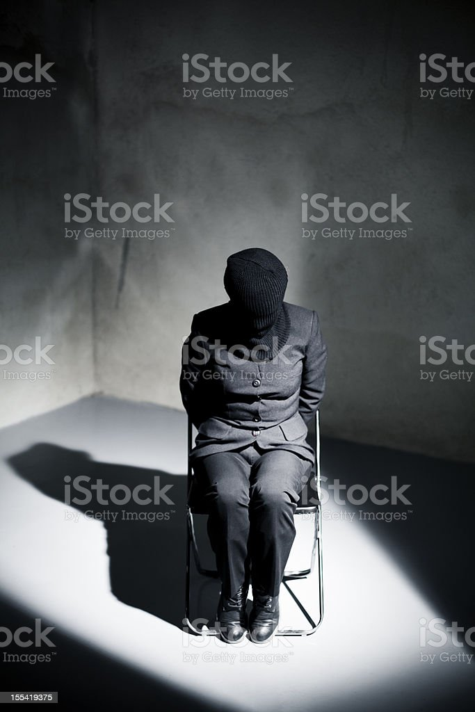 Prisoner tied to chair in cell spotlight stock photo