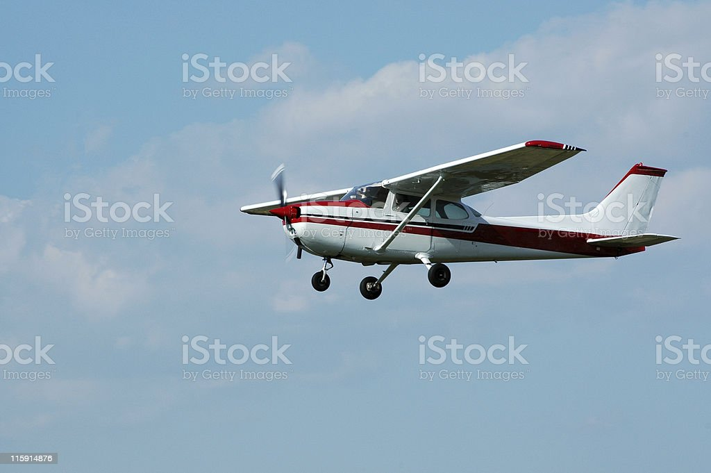 private airplane Cessna 172 in blue sky with white clouds stock photo