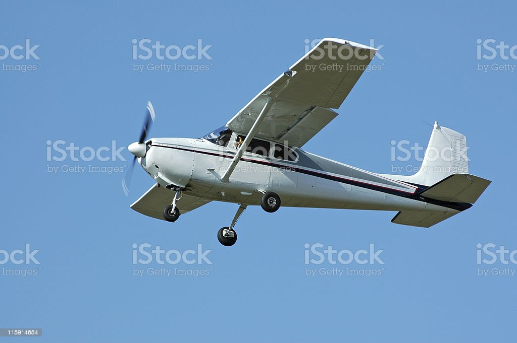 private airplane Cessna 182 flying in clear blue sky stock photo