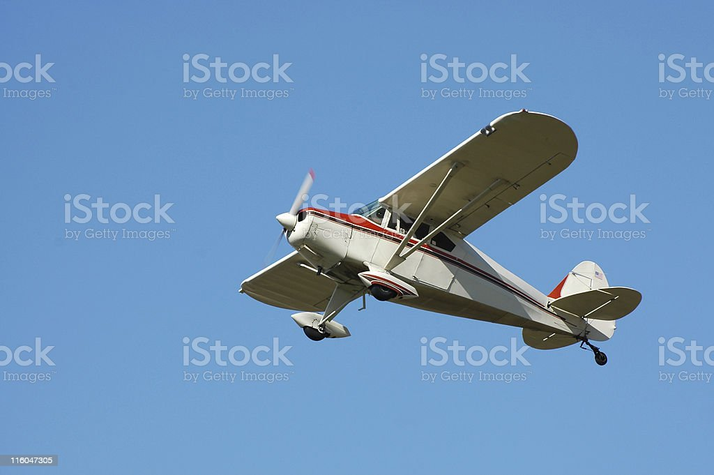 private airplane Fairchild M62A flying in clear blue sky stock photo