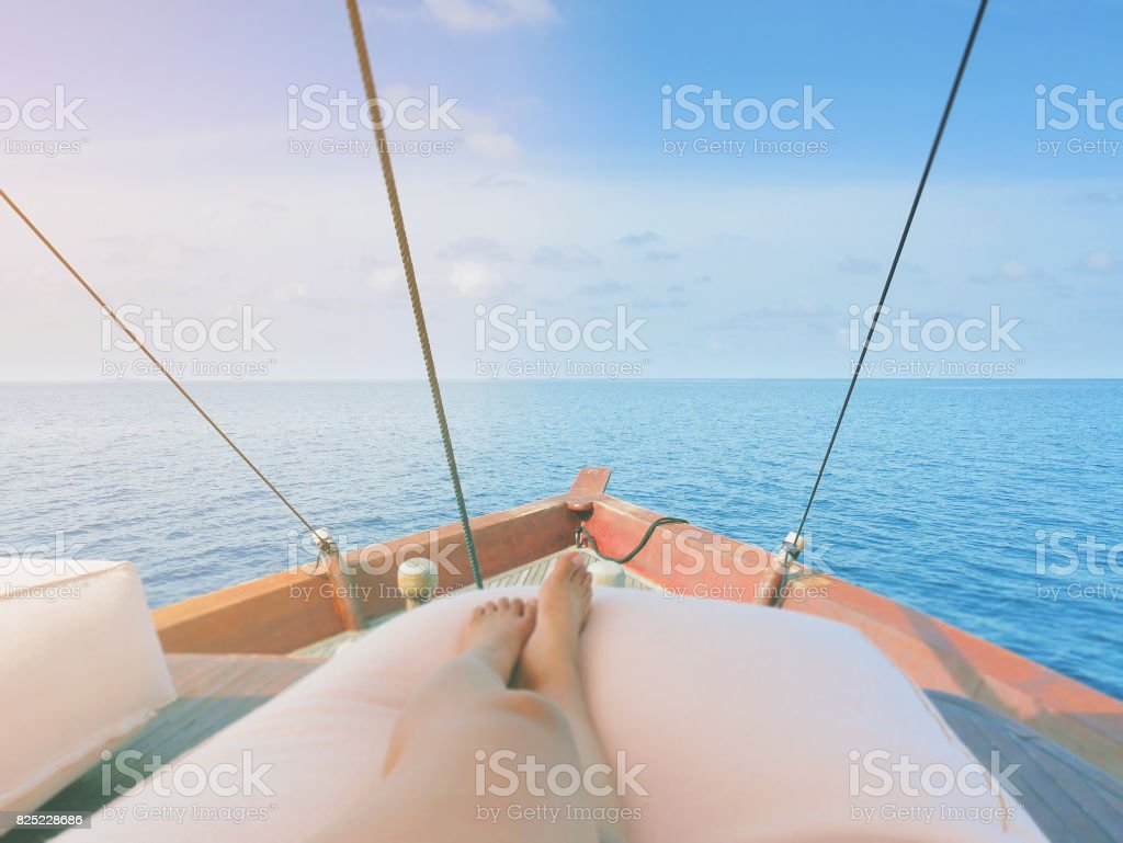 Private boat trip on open sea. Image shows legs of a woman lying on a...