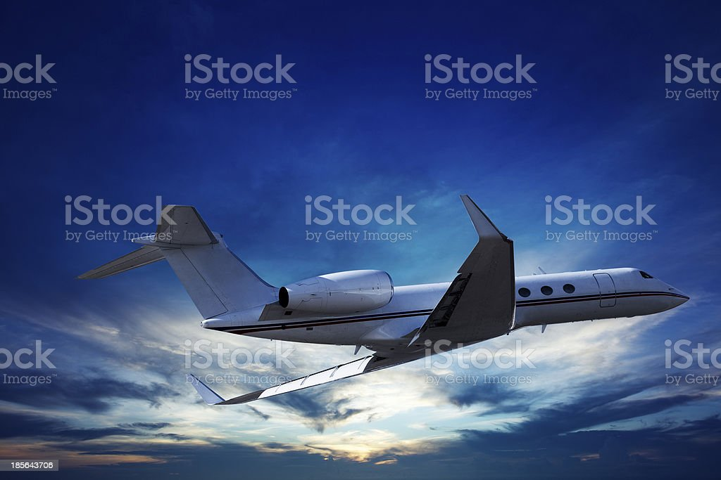 Private jet cruising at sunset stock photo