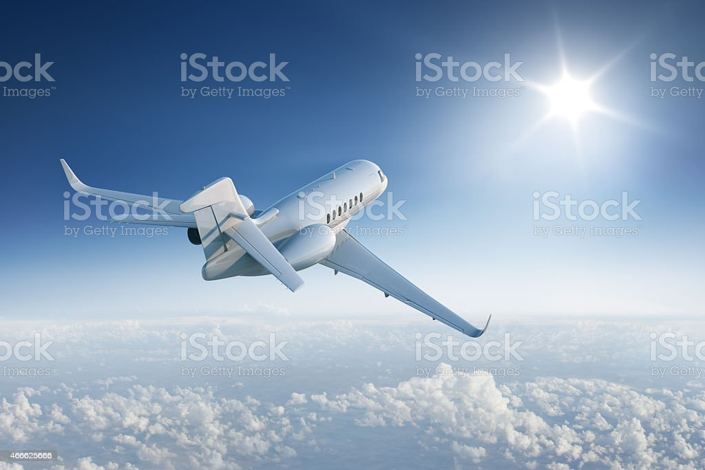 Private jet flying towards the sun in blue sky stock photo