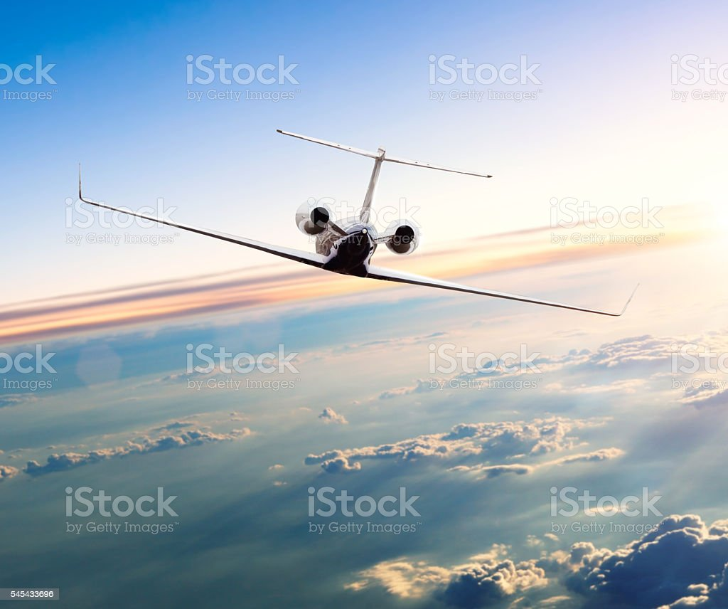 Private jet plane flying above clouds stock photo