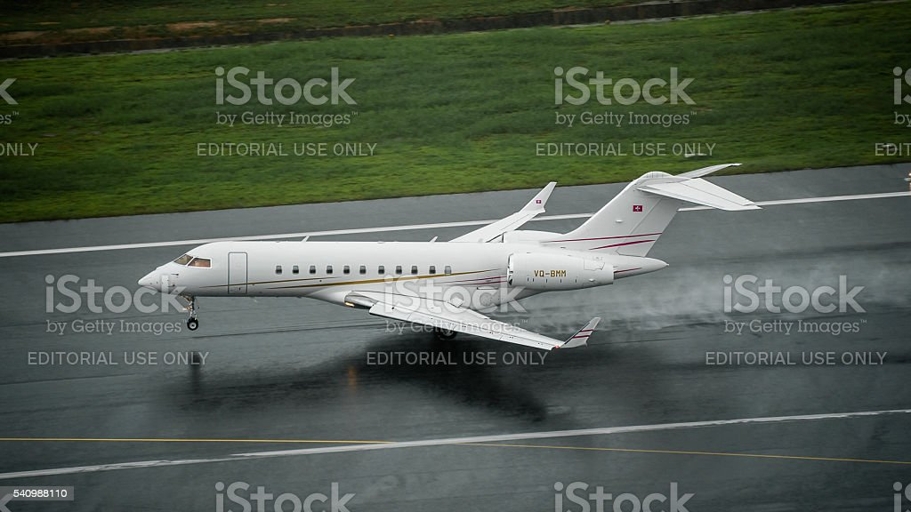Private jet type Bombardier global 5000 landing on wet runway stock photo