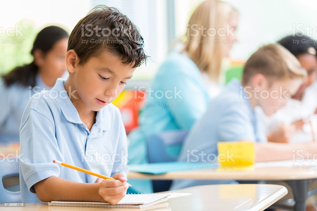 Private school student writes something in class stock photo