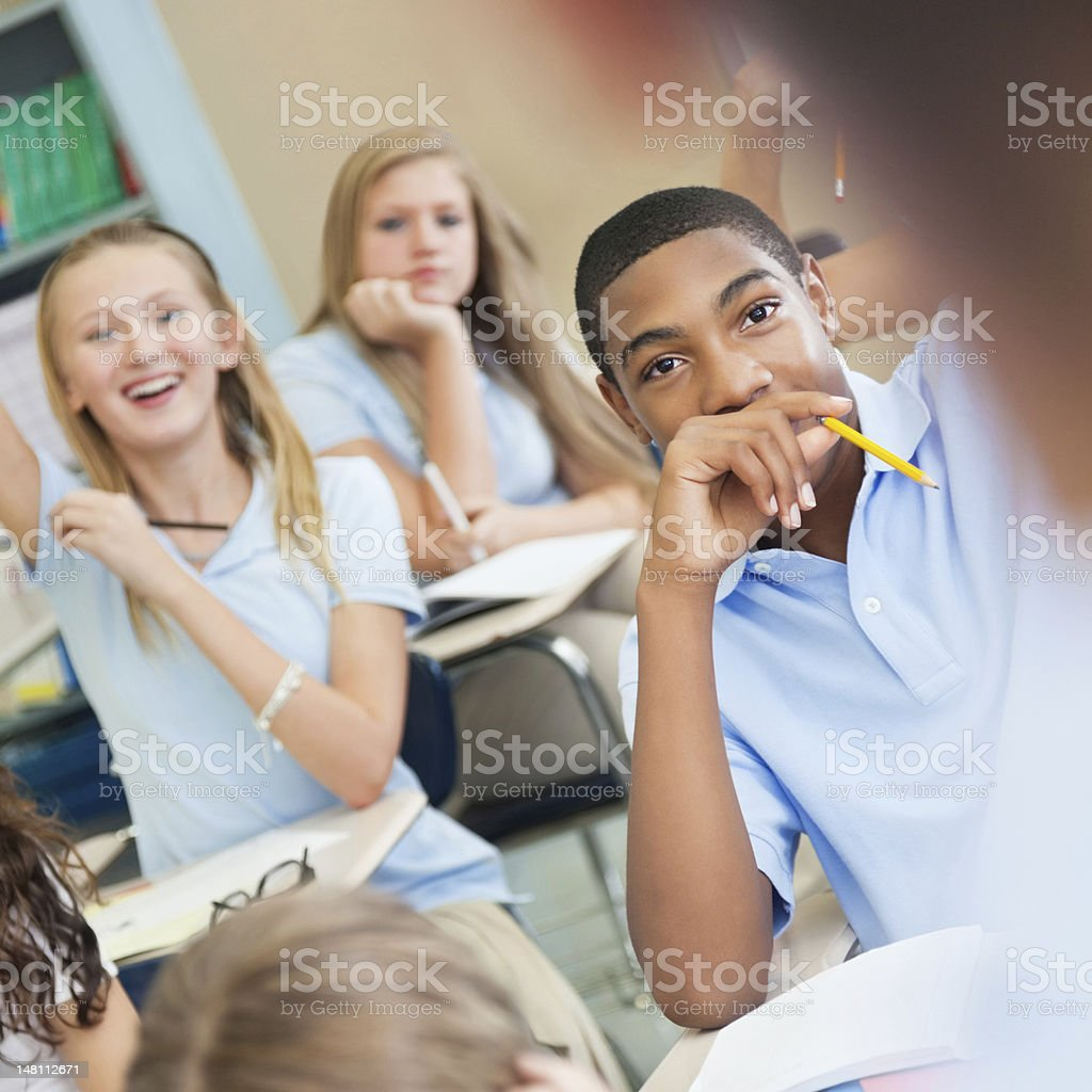 Private school students raising hands to answer teacher's question stock photo
