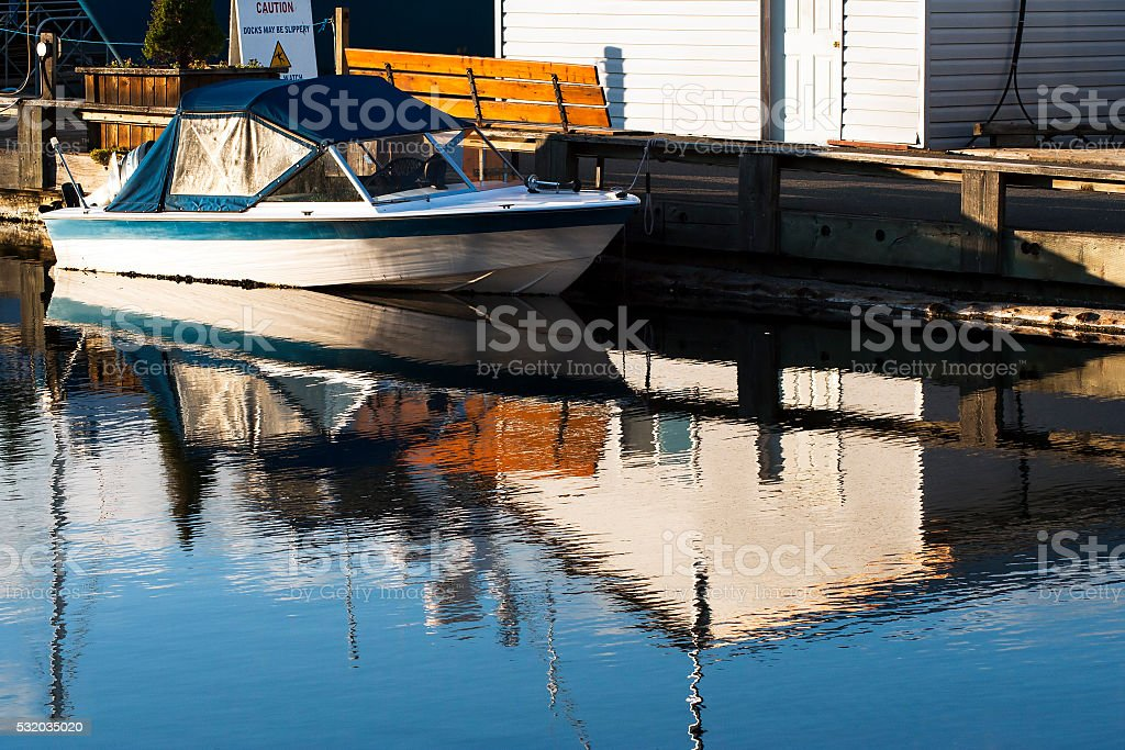 private speed boat docked by the boardwalk at harbour stock photo