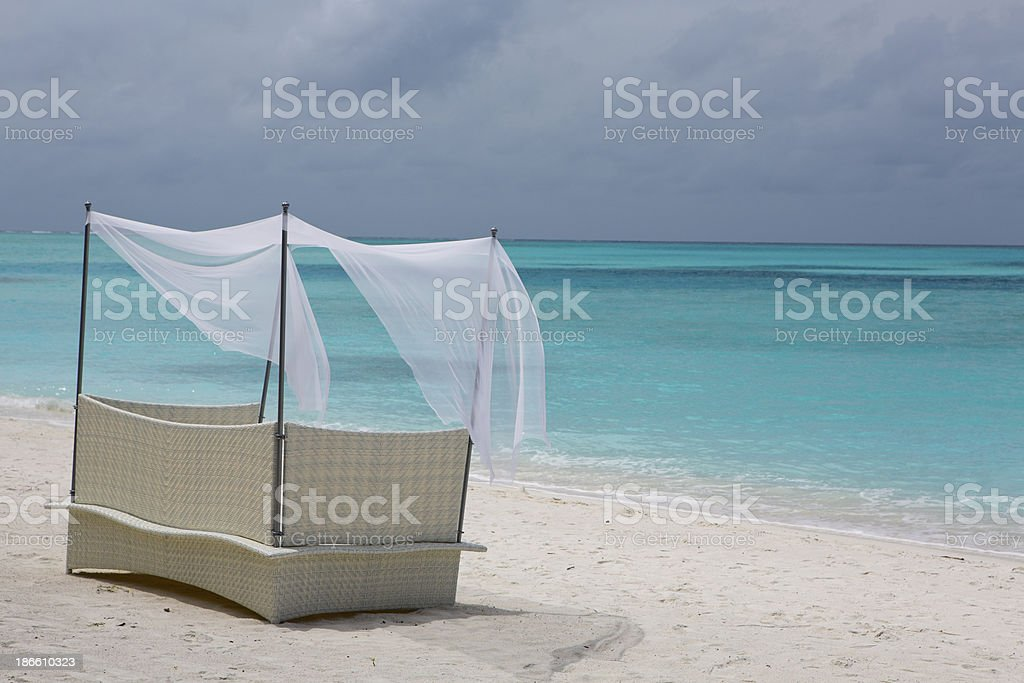 Private Wicker Bench on a White Sandy Beach in the Maldives royalty-free stock photo