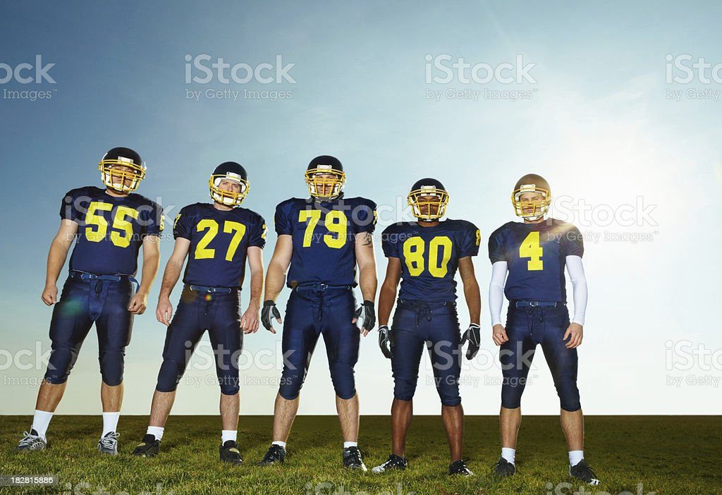 Pro American footballers standing against clear sky royalty-free stock photo