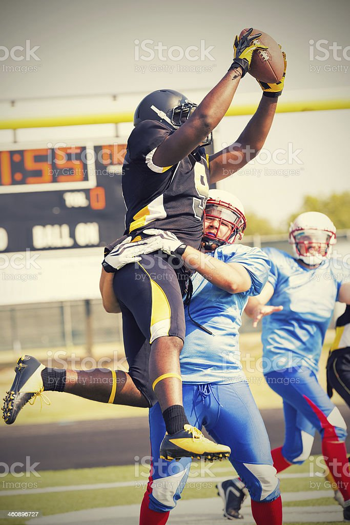 Pro football player jumping to receive ball after pass royalty-free stock photo