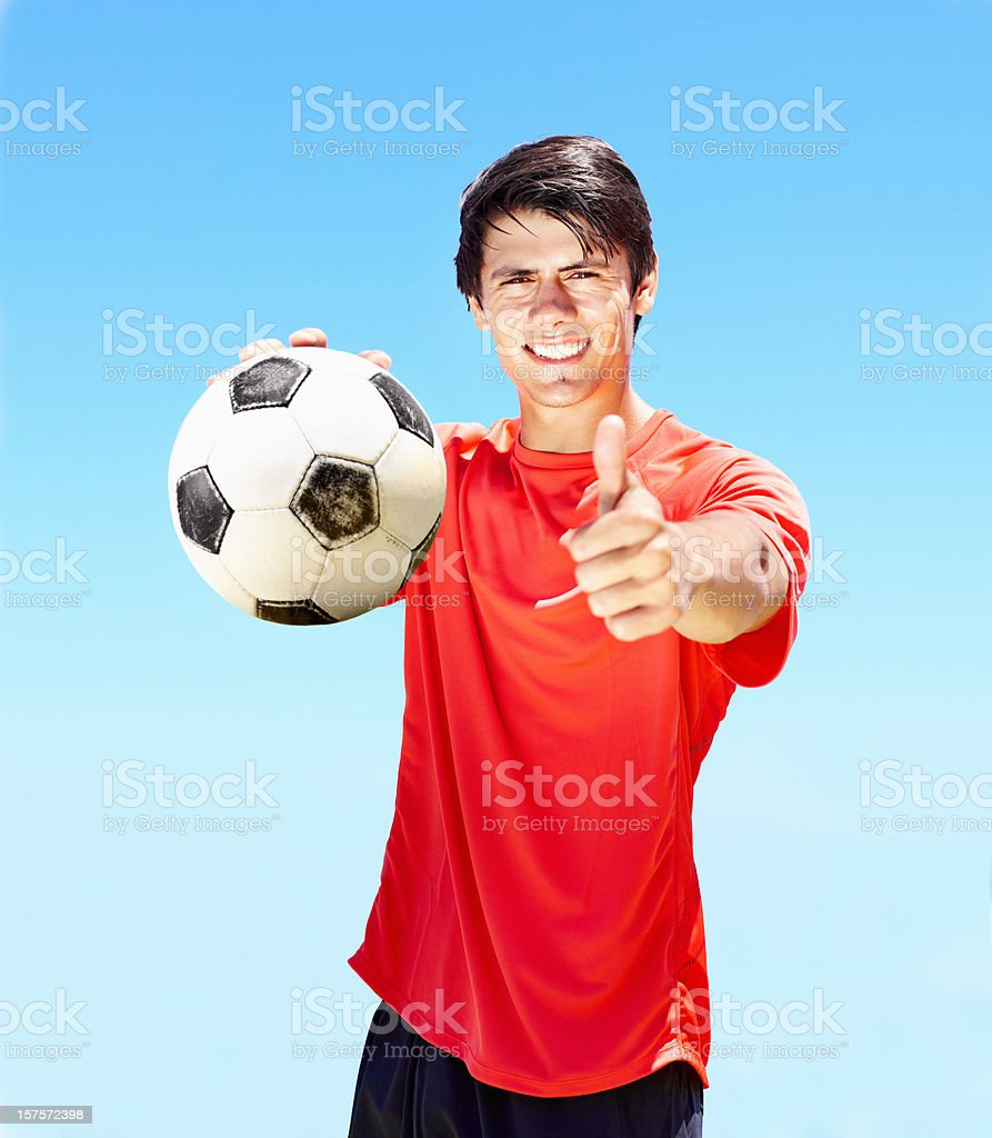 Pro footballer with football showing thumbs up sign royalty-free stock photo