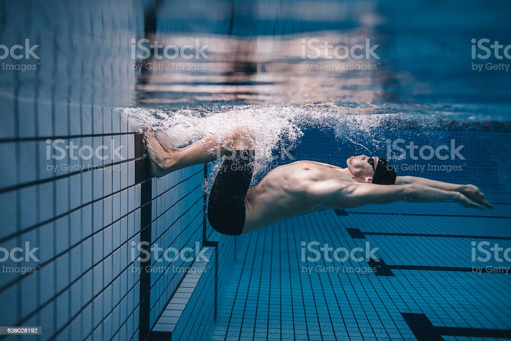 Pro male swimmer in action inside swimming pool stock photo