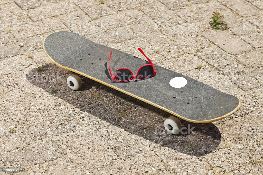 Pro skateboard with red sunglasses on the street. royalty-free stock photo