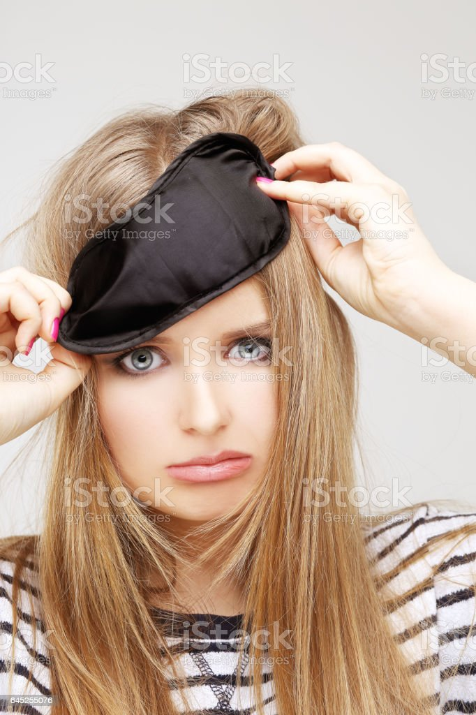 Problem.Crying girl.Girl with sleeping mask on her forehead stock photo