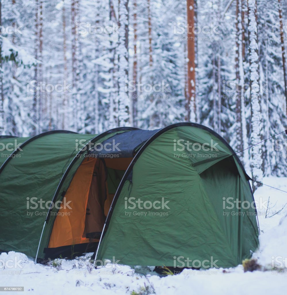 A process of camping in winter forest, setting a tent covered in snow, making a bonfire campfire and cooking food with portable gas cooker and fire, snowy landscape stock photo