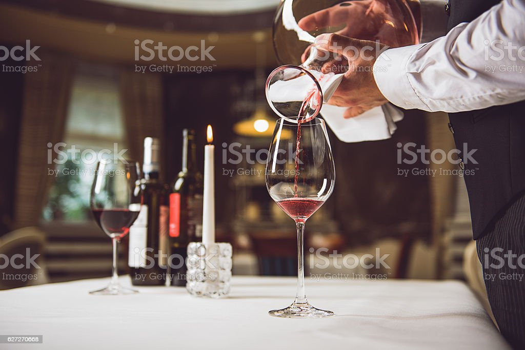 Process of filling glass with wine stock photo