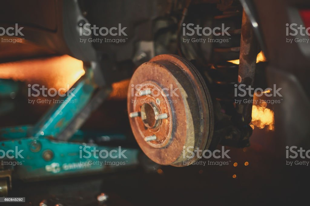 A process of new tire replacement, disc brake on car, repair in garage, automotive service station, mechanic changing a wheel and tires stock photo