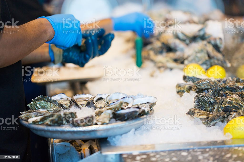 process of shucking oysters stock photo