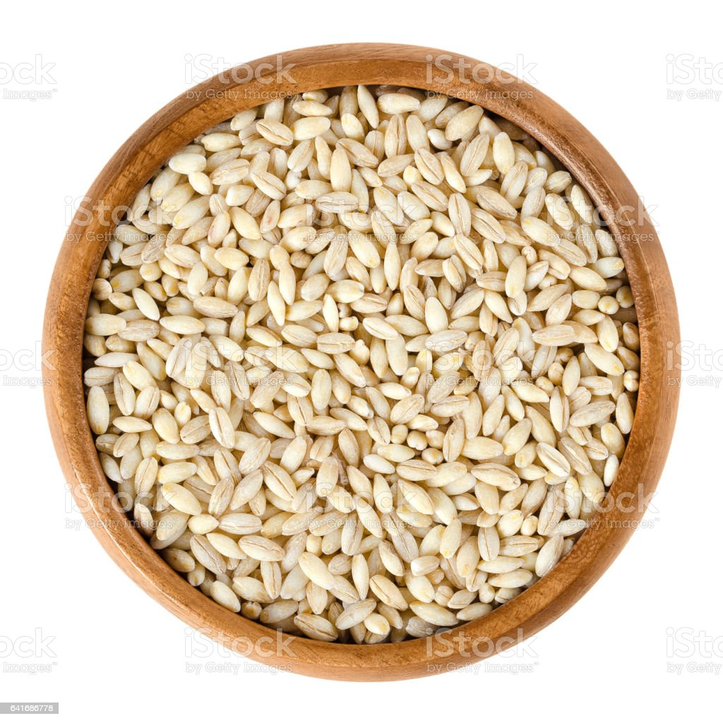 Processed pearl barley in wooden bowl over white stock photo