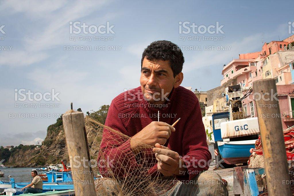 Procida (Naples), Italy: Fisherman Repairing Fishing Net stock photo