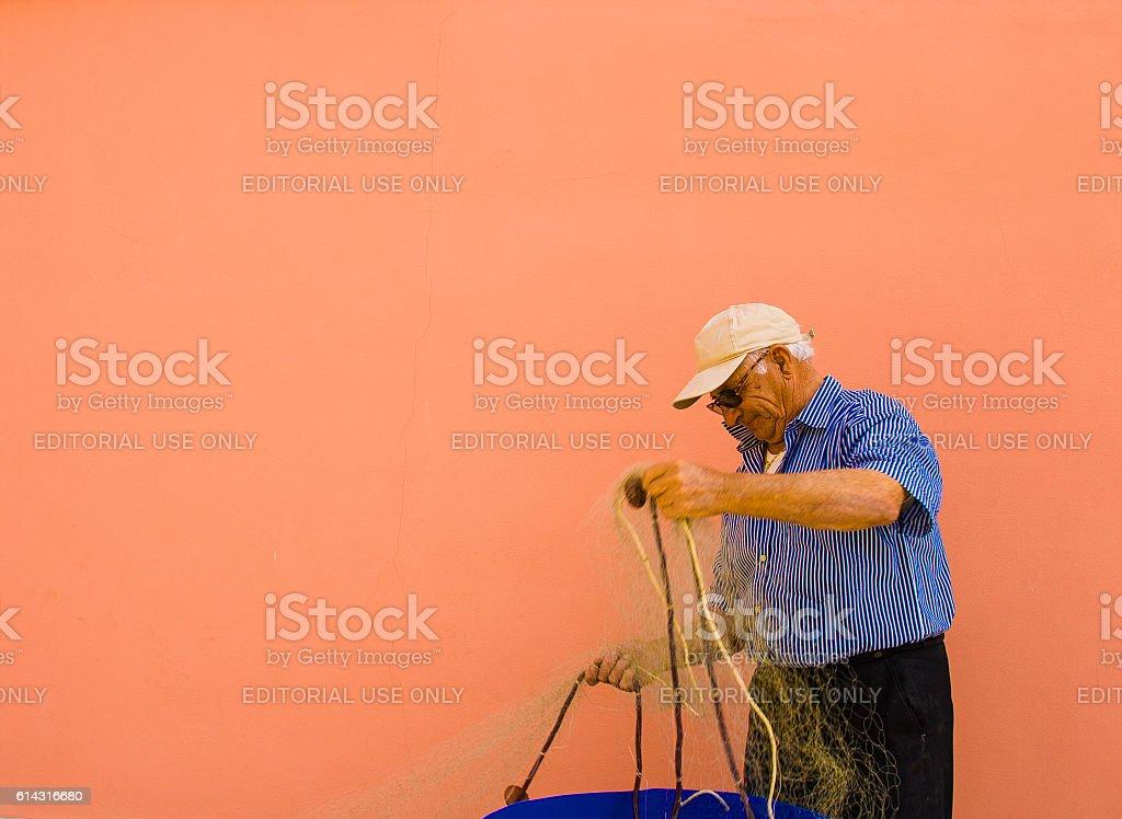 Procida (Naples), Italy: Fisherman Untangling Fishing Net, Orange Background stock photo