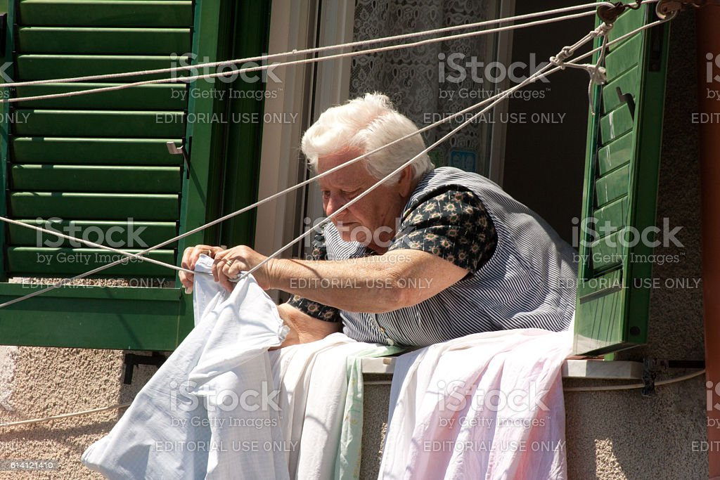 Procida (Naples), Italy: Senior Woman Leans From Window Hanging Sheets stock photo