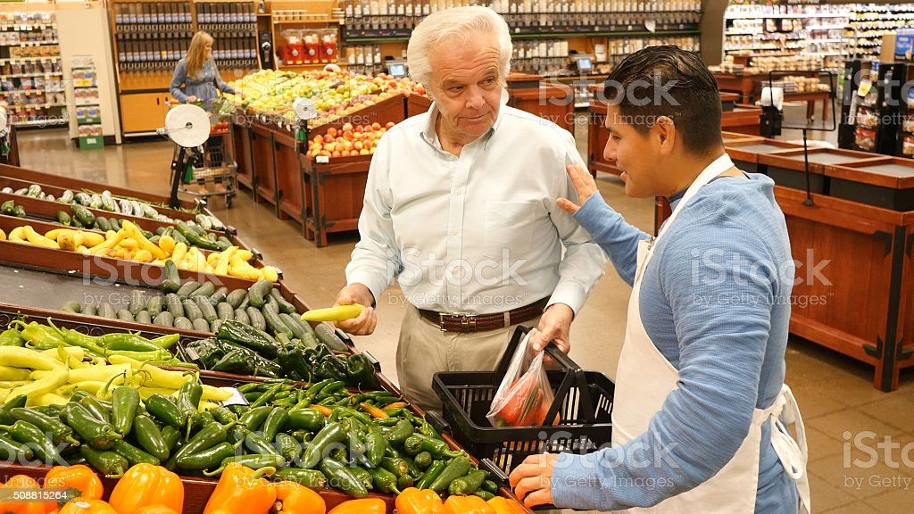 Produce manager in supermarket assists customer stock photo