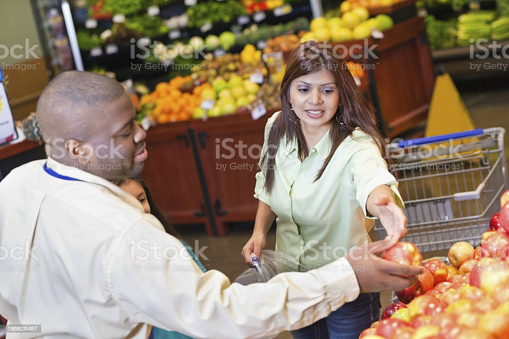 Produce worker helping customer at grocery store royalty-free stock photo