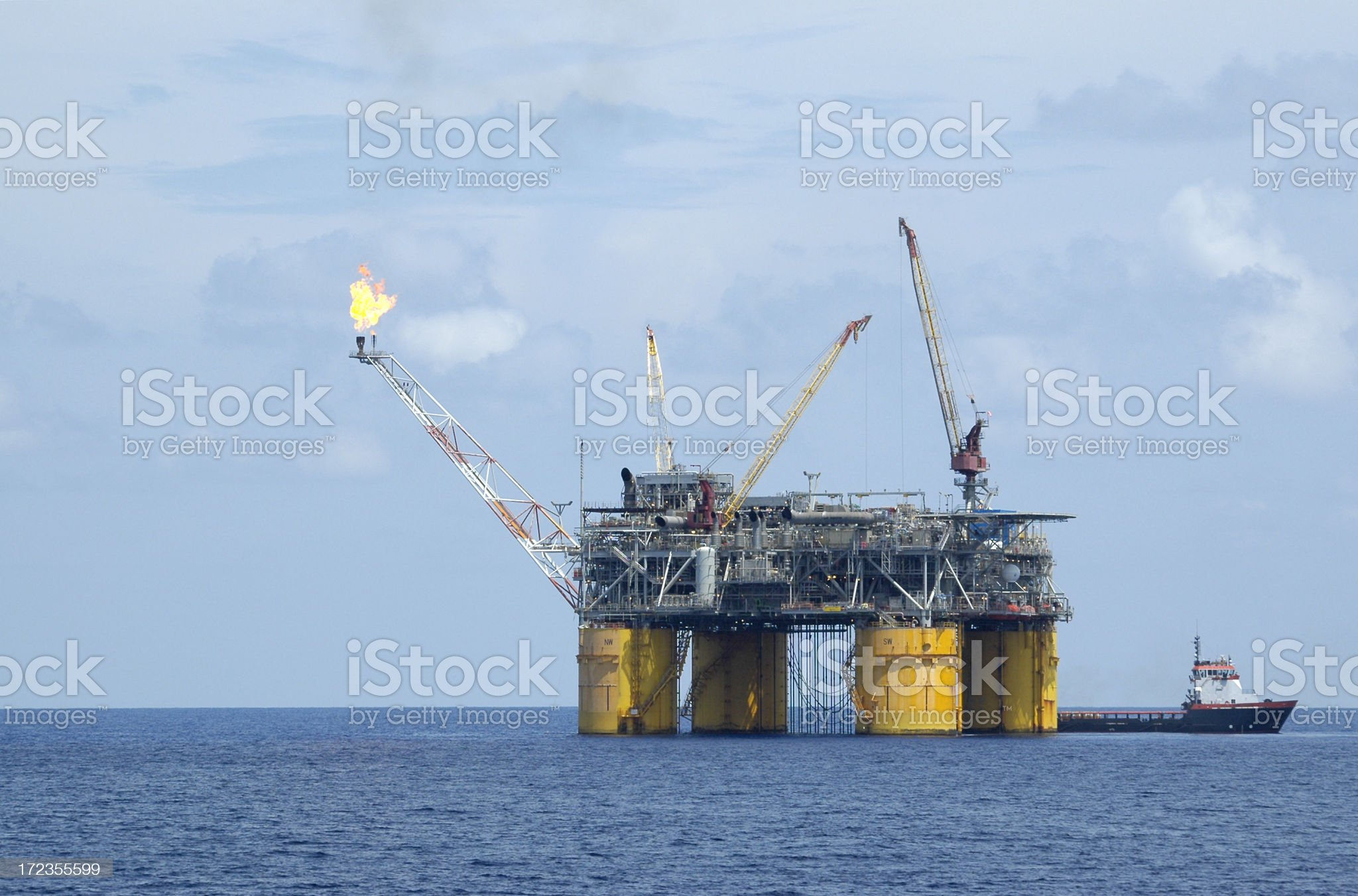Production platform with flare. Oil rig and supply vessel. royalty-free stock photo