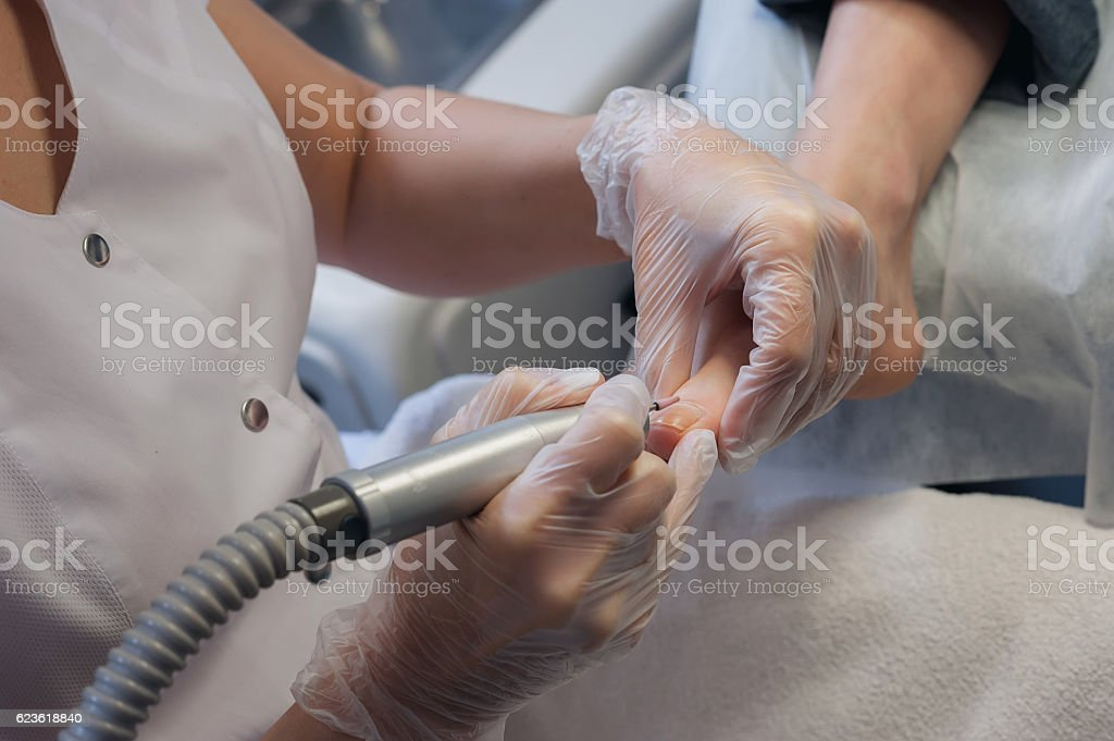 profesional nail technician sanding nails with machine stock photo