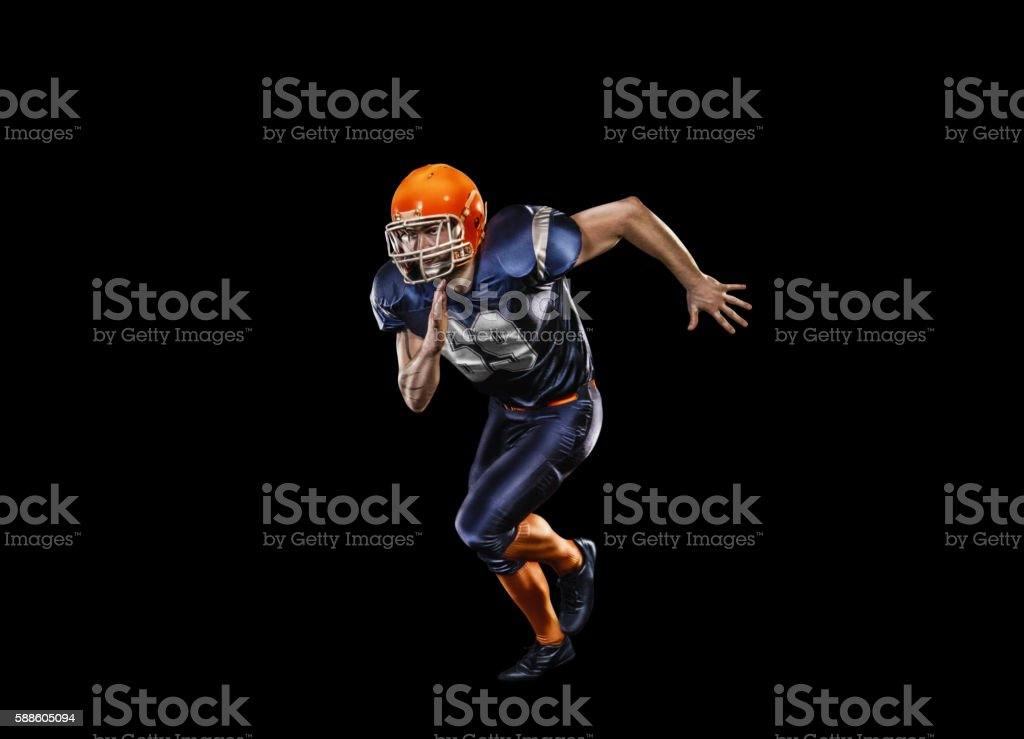 Professional american football player in action isolated on the black stock photo