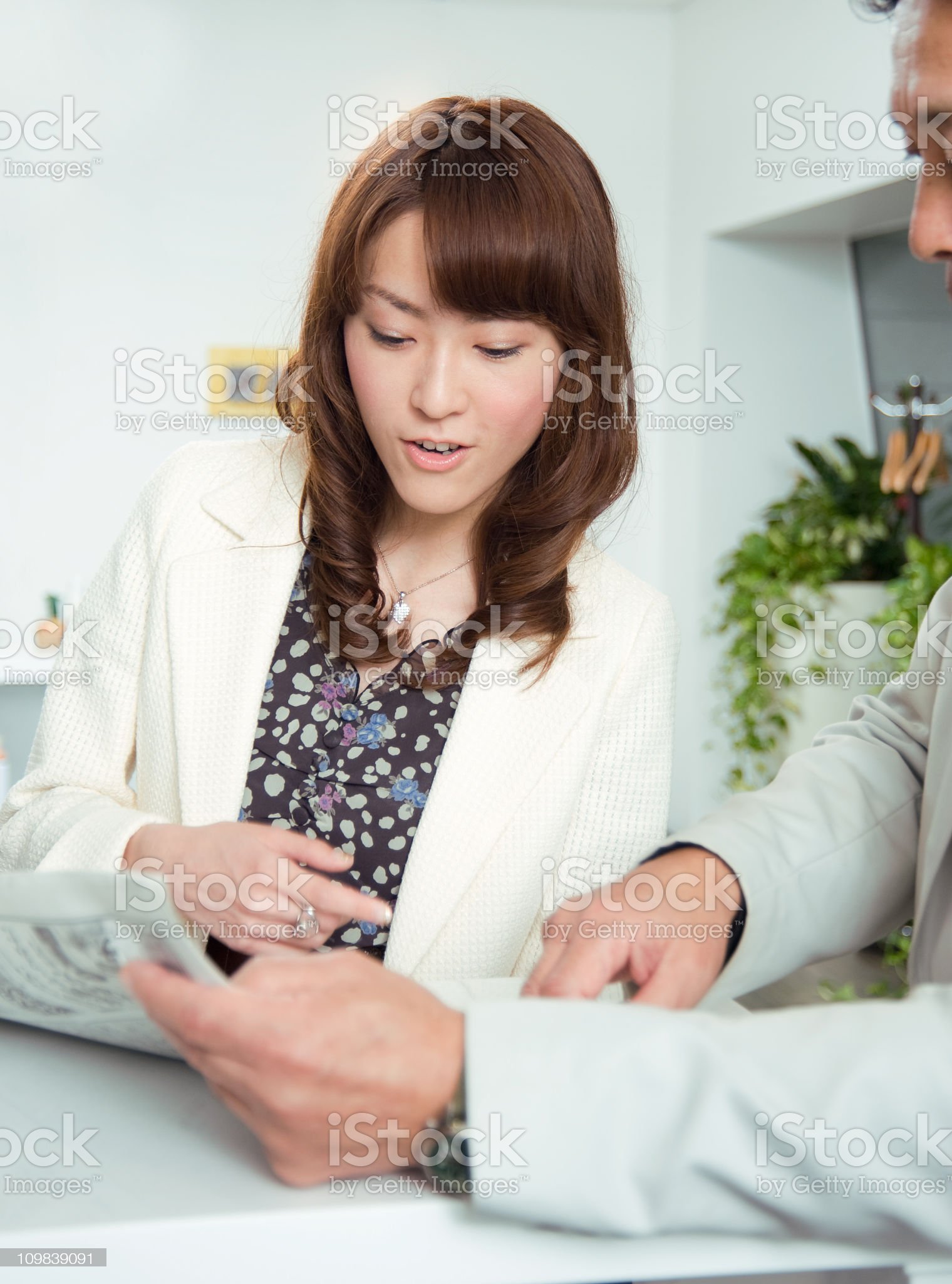 Professional Asian Business People looking Over Papers royalty-free stock photo