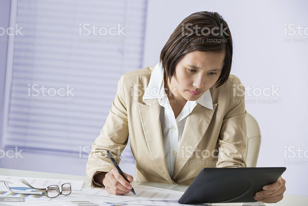 Professional Asian woman working with digital tablet in office stock photo