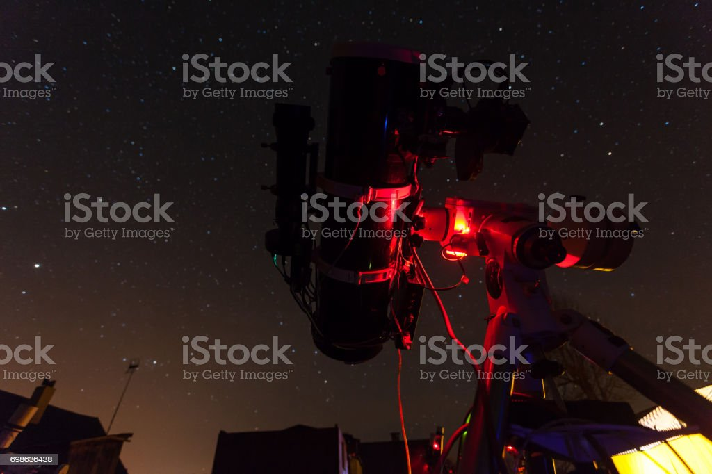 Professional astrophotography telescope taking pictures under night sky stock photo