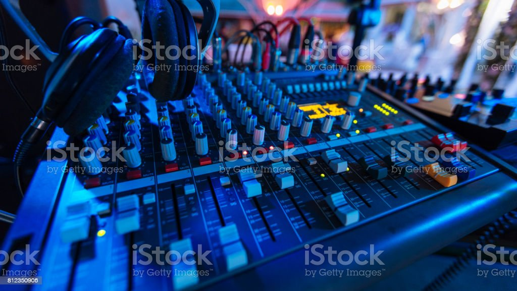 Professional audio mixing console with fader and adjusting knobs - radio / TV broadcasting that hand adjusting audio mixer stock photo