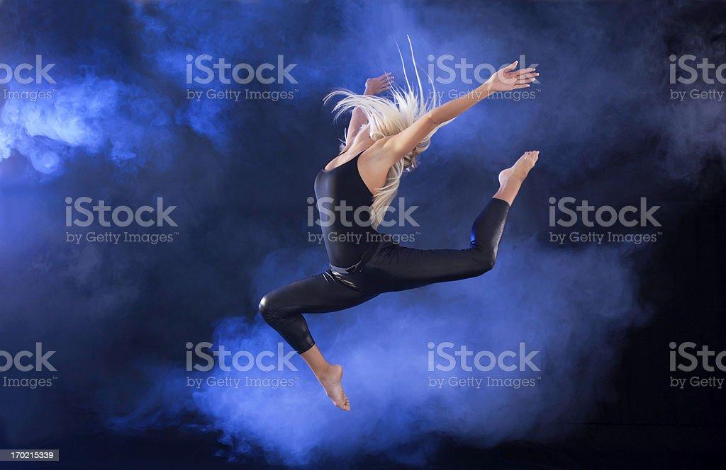 Professional ballerina jumping through the fog. royalty-free stock photo