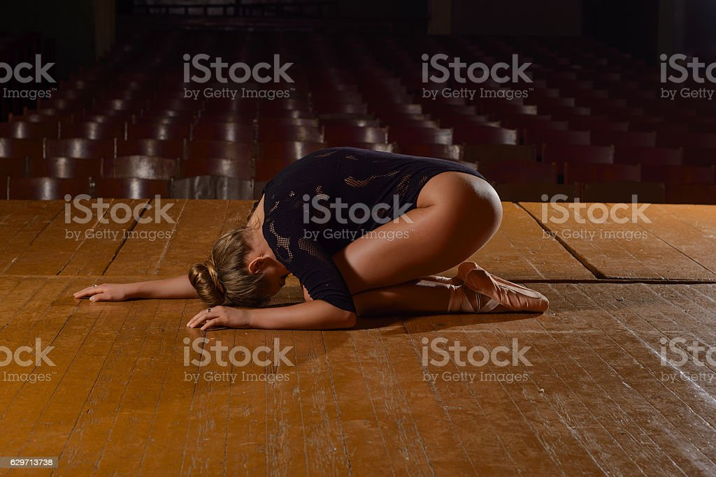 Professional ballet dancer lying on the stage after the performance. stock photo