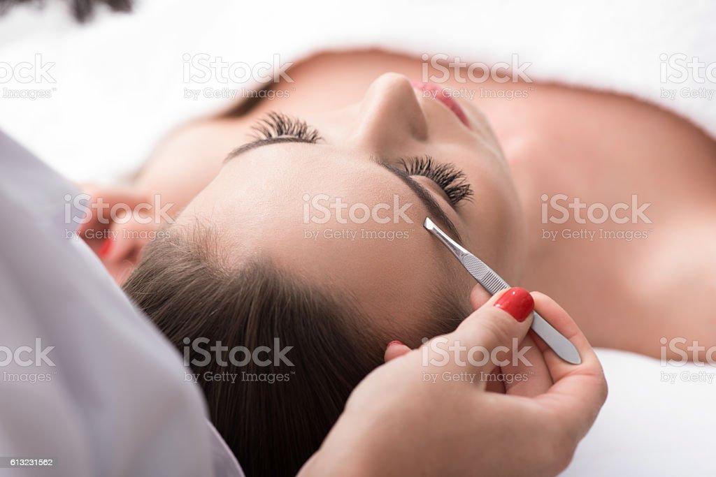 Professional beautician tweezing human brows stock photo