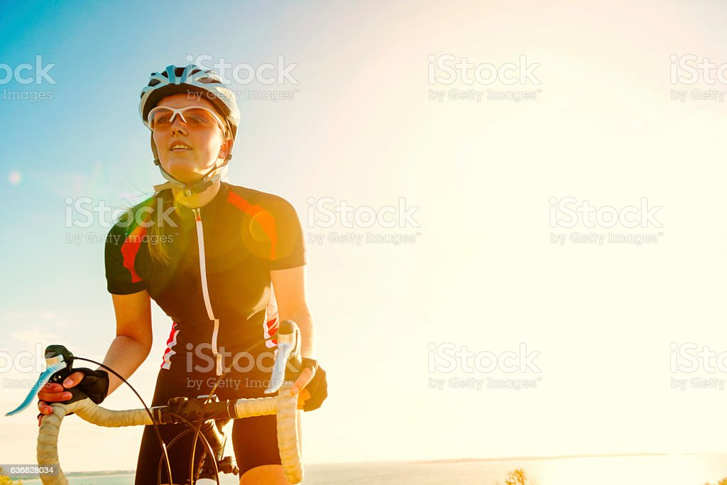 Professional bicycle rider smiles as she pushes the bike forward stock photo