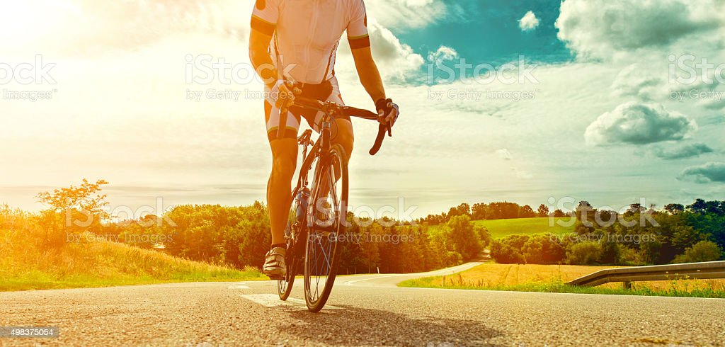 Professional bicyclist rides his bike on a country road stock photo