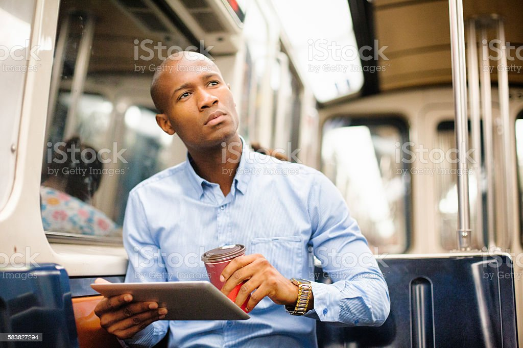 Professional black man distracted by game on subway checks location stock photo