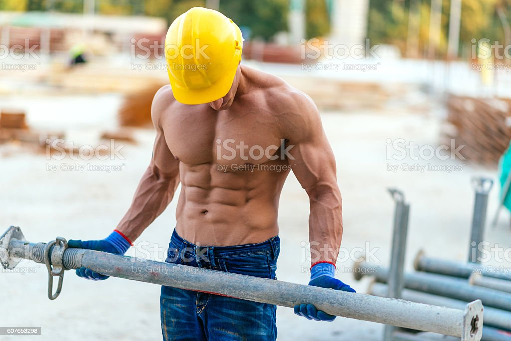 Professional body builder on construction site with heavy load stock photo