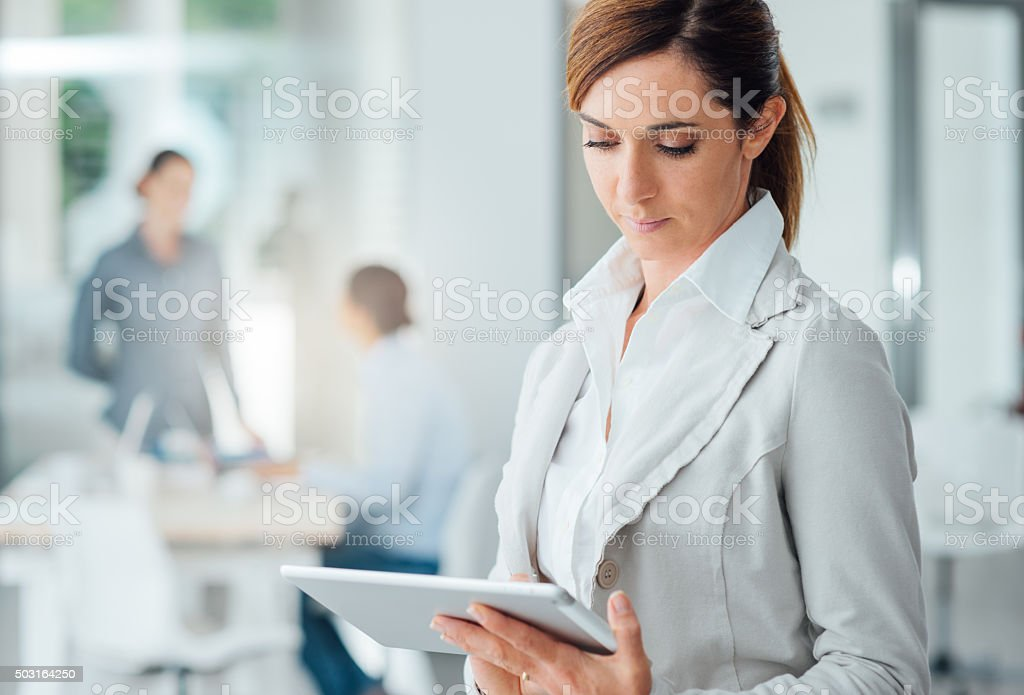 Professional business woman using a digital tablet stock photo
