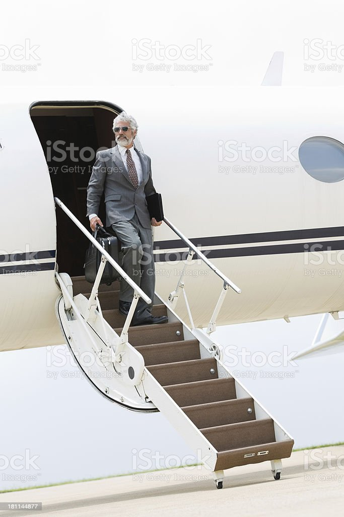 Professional businessman on steps of private jet royalty-free stock photo