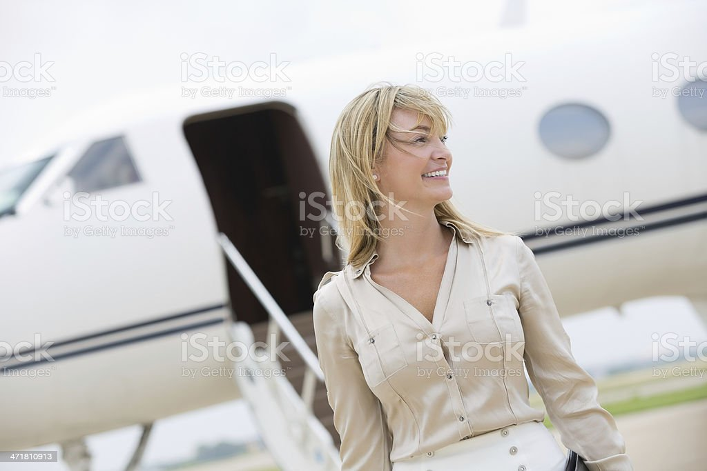 Professional businesswoman exiting private jet royalty-free stock photo