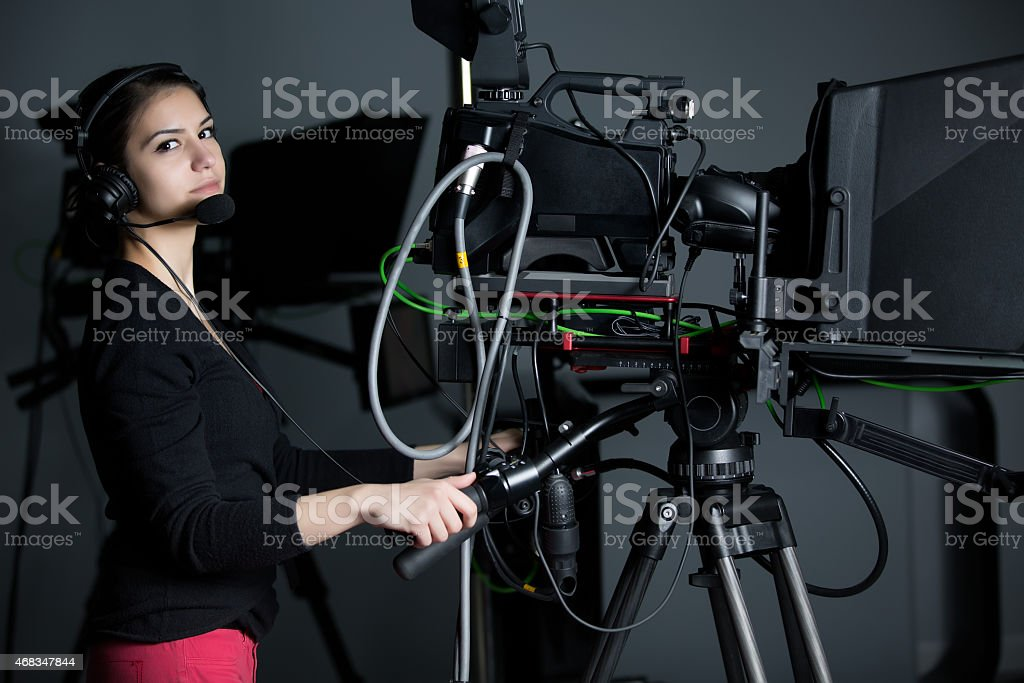Professional camera operator with headphones and camera in television news stock photo